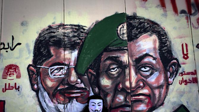 """FILE - In this Saturday, Dec. 8, 2012 file photo, an Egyptian protester wears a Guy Fawkes mask while posing for a photo next to a mural painted overnight on the exterior  wall of the presidential palace depicting president Mohammed Morsi, left, former military council ruler Hussein Tantawi, center and ousted President Mubarak with Arabic that reads """"no, the brotherhood's constitution is not valid,"""" in Cairo, Egypt. Some six months since becoming the first democratically elected president of Egypt, Morsi is widely accused of having abandoned pledges of inclusive government for doctrinaire and authoritarian ways. (AP Photo/Nasser Nasser, File)"""