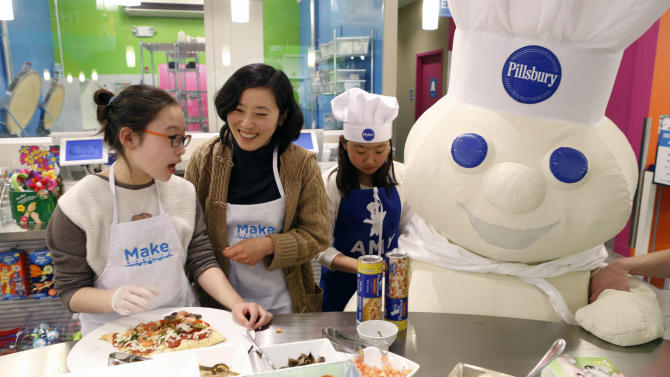 IMAGE DISTRIBUTED FOR PILLSBURY - Families met the Doughboy during a Pillsbury pizza-making adventure at Make Meaning Legacy Place on Friday, April 5, 2013, in Dedham, Mass. Moms and kids learned how to add simple twists to traditional pizza by flavoring up the crust and used their creativity to decorate aprons, paint pizza plates and add pizza toppings. (Bizuayehu Tesfaye/ AP Images for Pillsbury)
