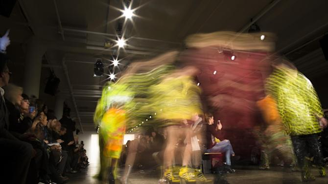 In this photo made with a long exposure, models walk the runway at the Jeremy Scott Fall 2013 fashion show during Fashion Week, Wednesday, Feb. 13, 2013, in New York. (AP Photo/John Minchillo)