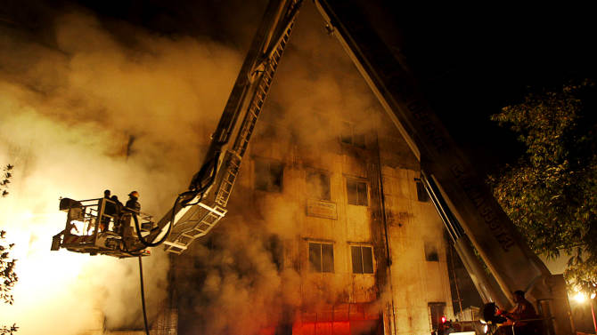 Firefighters battle a fire at a garment factory in the Savar neighborhood in Dhaka, Bangladesh, late Saturday, Nov. 24, 2012. At least 112 people were killed in a fire that raced through the multi-story garment factory just outside of Bangladesh's capital, an official said Sunday. (AP Photo/Hasan Raza)
