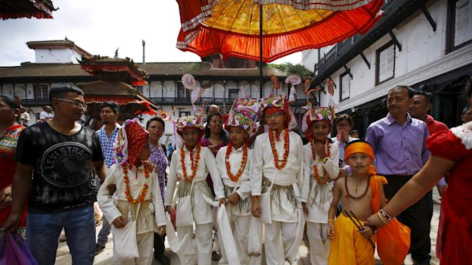 Boys dressed in white depicting holy cows participate in a parade to mark the Gaijatra Festival, also known as the festival of cows, in Kathmandu