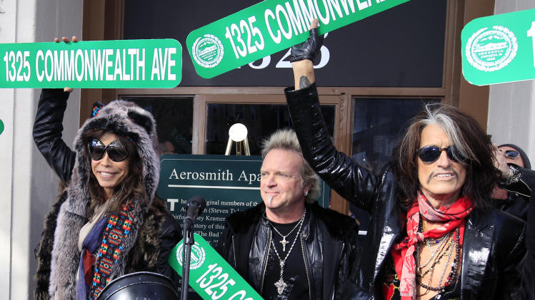 Aerosmith members, from left, Steven Tyler, Joey Kramer and Joe Perry hold up signs Monday, Nov. 5, 2012 at an address in Boston's Allston neighborhood which was their home in the early 1970's. Aerosmith later gave a free concert in front of the building. (AP Photo/Elise Amendola)