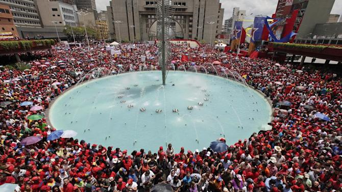 Supporters of Venezuela's acting President Nicolas Maduro gather around a fountain outside the national electoral council as he registers his candidacy for president to replace late President Hugo Chavez in Caracas, Venezuela, Monday, March 11, 2013.  Elections were announced to take place on April 14, after the death of Chavez on March 5.  (AP Photo/Ariana Cubillos)