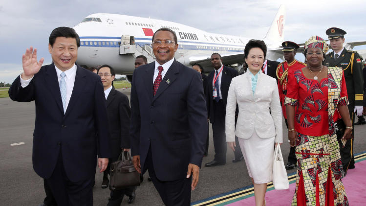 In this photo released by China's Xinhua News Agency, Chinese President Xi Jinping, left, and his wife Peng Liyuan, second right, are welcomed by Tanzanian President Jakaya Mrisho Kikwete, second left, and his wife Salma Kikwete, right, upon their arrival in Dar es Salaam, Tanzania, Sunday, March 24, 2013. Glamorous new first lady Peng has emerged as a Chinese diplomatic star, charming audiences and cutting a distinct profile from her all-but-invisible predecessors on her debut official trip abroad. (AP Photo/Xinhua, Lan Hongguang) NO SALES