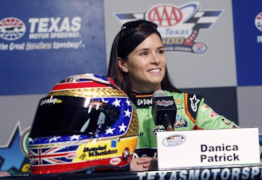 Danica Patrick listens to a question next to a tribute helmet to late-IndyCar driver Daniel Wheldon during a media availability at Texas Motor Speedway in Fort Worth, Texas,  Friday, Nov. 4, 2011. Patrick, who is moving full time to NASCAR next season, is racing Saturday for the first time since the IndyCar Series finale at Las Vegas three weeks ago. (AP Photo/LM Otero)