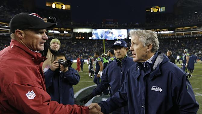 Arizona Cardinals head coach Ken Whisenhunt, left, shakes hands with Seattle Seahawks head coach Pete Carroll after  an NFL football game in Seattle, Sunday, Dec. 9, 2012. The Seahawks won 58-0. (AP Photo/John Froschauer)