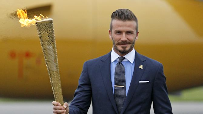 """FILE This file photo of Friday May 18, 2012 shows Britain's David Beckham holding the Olympic torch during the ceremony to mark the arrival of the Olympic flame to Britain from Greece, at RNAS Culdrose, in Cornwall, England.  Former England captain David Beckham has failed to make the British football team for the London Olympics. The Los Angeles Galaxy midfielder made Britain coach Stuart Pearce's shortlist of 35 but wasn't selected for the final 18-man squad as one of three players over the age of 23 allowed to compete in the games. """"Everyone knows how much playing for my country has always meant to me, so I would have been honored to have been part of this unique Team GB squad,"""" the 37-year-old Beckham said Thursday June 28, 2012 in a statement to The Associated Press. (AP Photo/Alastair Grant)"""