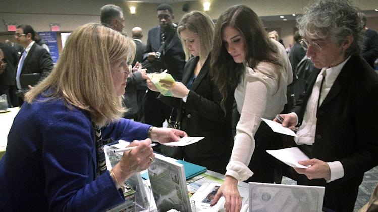 In this Wednesday, Oct. 24, 2012, photo, Patricia Mazza, left, meets job seekers, including recent college grads Ashley Deyo, 22, second from left, and Chyna Dama, 23, second from right, during a National Career Fairs' job fair, in New York. Weekly applications for U.S. unemployment benefits dropped 9,000 last week to a seasonally adjusted 363,000, the Labor Department said Thursday, Nov. 1, 2012. The level is consistent with modest hiring. (AP Photo/Bebeto Matthews)