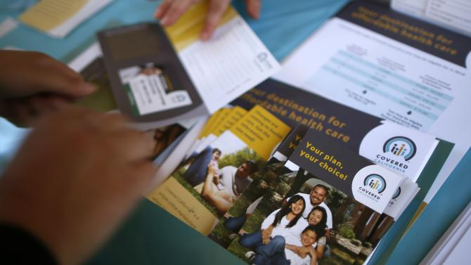 People sign up for health insurance information at a Covered California event in Los Angeles