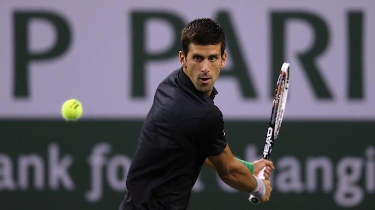 Novak Djokovic of Serbia returns a shot to Victor Hanescu of Romania during the BNP Paribas Open at Indian Wells Tennis Garden in California, on March 9, 2014