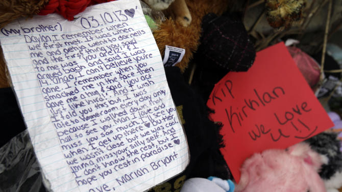 A note rests on a memorial where six teens died early Sunday in Warren, Ohio, on Monday, March 11, 2013. Two teens who escaped a crash that killed six friends in a swampy pond wriggled out of the wreckage by smashing a rear window and swimming away from the SUV, a state trooper said Monday. (AP Photo/Tony Dejak)