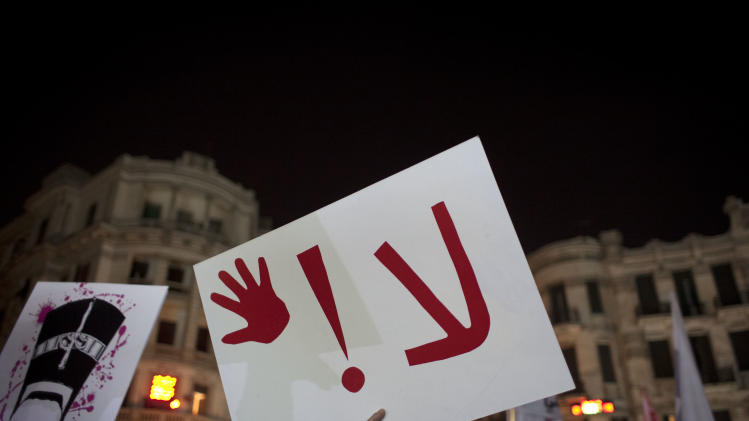 "An Egyptian woman activist holds a placard that reads ""no,"" while taking part in a protest for women against sexual harassment and against the Islamist dominated Shura Council blaming women for the attacks against them, in Cairo, Egypt, Tuesday, Feb. 12, 2013. (AP Photo/Nasser Nasser)"