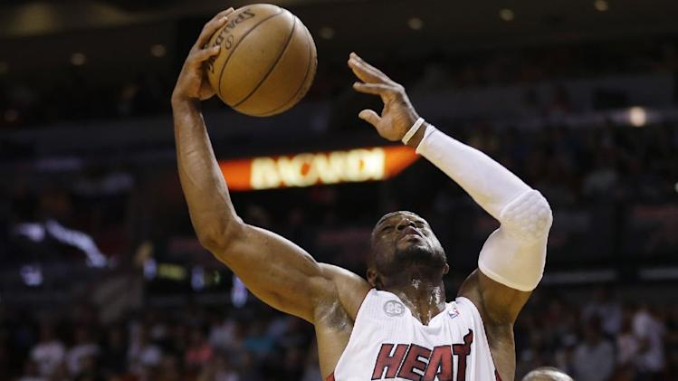 MIami Heat's Dwywane Wade (3) slides past Detroit Pistons' Rodney Stuckey (3) for two points during the first half of a NBA basketball game in Miami, Friday, March 22, 2013. (AP Photo/J Pat Carter)