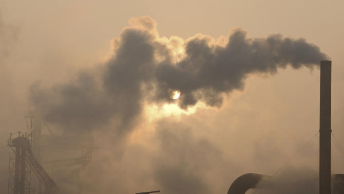 """FILE - Smoke pours from a chimney at a cement plant in Binzhou city, in eastern China's Shandong province, Thursday, Jan. 17, 2013. Scientists from around the world have gathered in Stockholm in September 2013 for a meeting of a U.N. panel on climate change and will probably issue a report saying it is """"extremely likely"""" - which they define in footnotes as 95 percent certain - that humans are mostly to blame for temperatures that have climbed since 1951. (AP Photo)"""