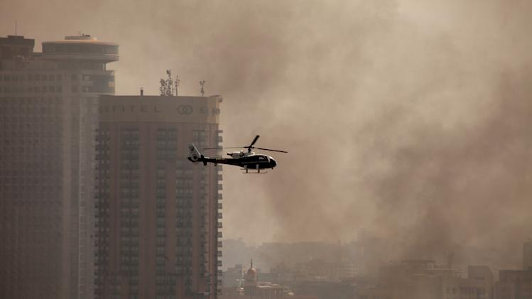 An Egyptian police helicopter flies through smoke from fires set by protesters at a police officers club and the Egyptian Soccer Federation  following a court verdict in Cairo, Egypt, Saturday, March 9, 2013. Fans of Cairo's Al-Ahly club have stormed Egypt's soccer federation headquarters and a nearby police club and set them ablaze after a court acquitted seven of nine police official on trial for their alleged part in deadly stadium melee. (AP Photo/Maya Alleruzzo)