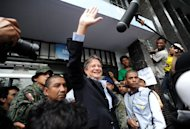 Ecuadorian opposition candidate Guillermo Lasso waves after casting his vote during general elections in Guayaquil on February 17, 2013. Lasso, who had around 24% of the vote in the preliminary tally, conceded defeat shortly after the results were announced