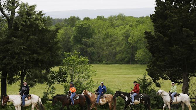 In this Friday, May 24, 2013 photo, mounted visitors tour Gettysburg National Military Park, in Gettysburg, Pa. Tens of thousands of visitors are expected for the 10-day schedule of events that begin June 29 to mark 150th anniversary of the Battle of Gettysburg that took that took place July 1-3, 1863. (AP Photo/Matt Rourke)