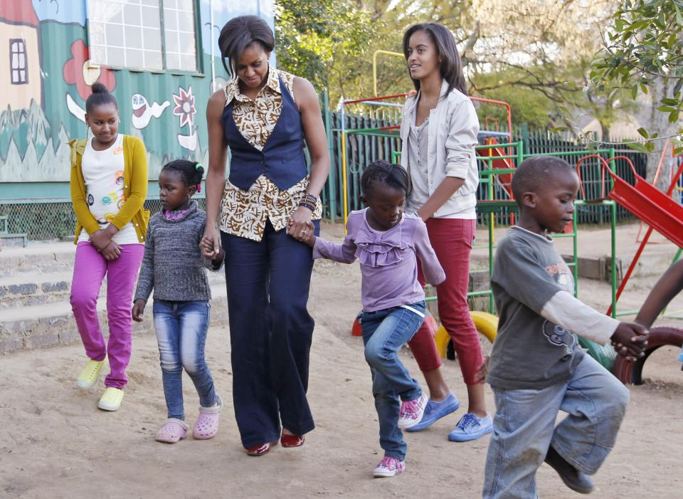 First lady Michelle Obama, and daughters Sasha and Malia, march with children during their visit to the Emthonjeni Community Center in Zandspruit Township, Johannesburg, South Africa, Tuesday, June 21, 2011. (AP Photo/Charles Dharapak, Pool)