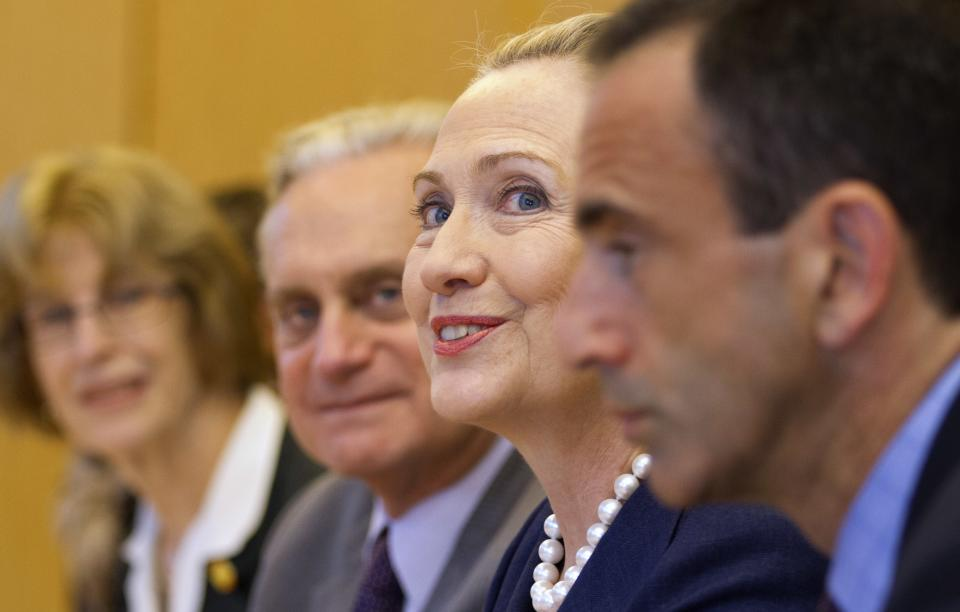 Surrounded by diplomats and staff, U.S. Secretary of State Hillary Rodham Clinton, second from right, meets with Turkey's Foreign Minister Ahmet Davutoglu, not pictured, in Istanbul, on Saturday, Aug. 11, 2012. (AP Photo/Jacquelyn Martin, Pool)