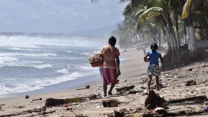 A woman and a girl walk along the beach covered in debris after Hurrican Odile hit the area, in Acapulco