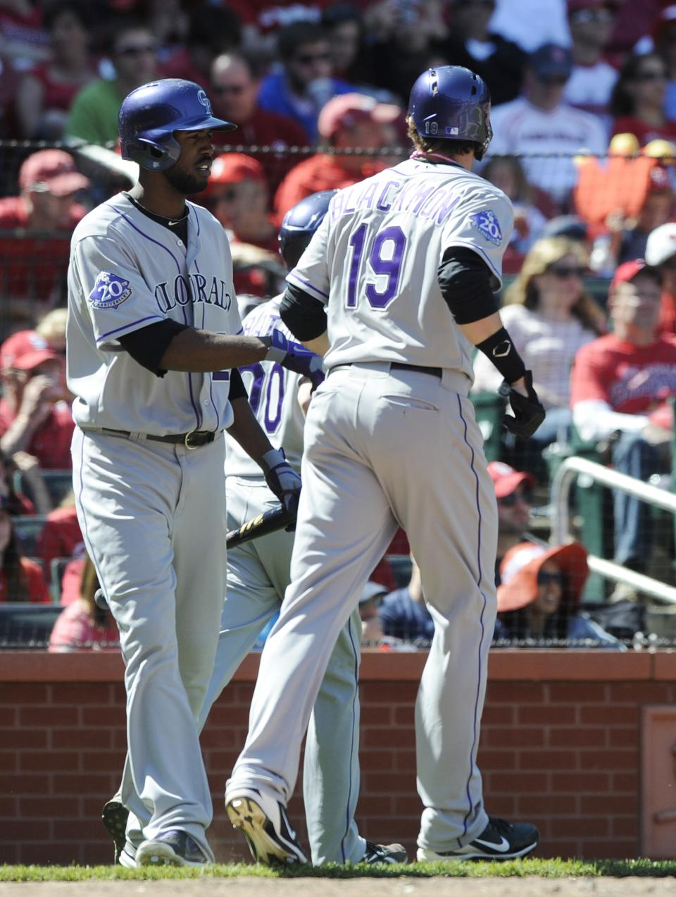 Colorado Rockies' Charlie Blackmon (19) is congratulated by teammate Dexter Fowler, left, after scoring on a three-run home run by by Reid Brignac against the St. Louis Cardinals in the eighth inning in a baseball game on Sunday, May 12, 2013, at Busch Stadium in St. Louis. (AP Photo/Bill Boyce)