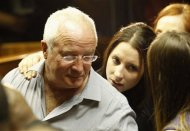 Oscar Pistorius's sister Aimee and father Henke confer during a break in court proceedings at the Pretoria Magistrates court, February 21, 2013. REUTERS/Siphiwe Sibeko