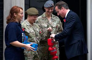 Prime Minister David Cameron (R) buys his remembrance…