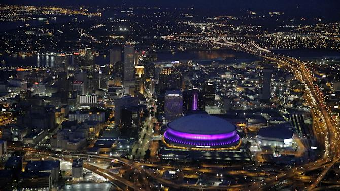 In this aerial photo, the Mercedes-Benz Superdome is lit up in purple lights Thursday, July 3, 2014 in New Orleans, in honor of Essence Festival headliner Prince, who performs on Friday, July 4. (AP Photo/Gerald Herbert)