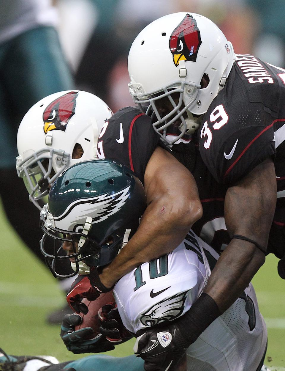 Philadelphia Eagles wide receiver DeSean Jackson, left, is tackled shy of the end zone by Arizona Cardinals safeties Kerry Rhodes, center, and James Sanders, right, to prevent a touchdown in the second quarter of an NFL football game on Sunday, Sept. 23, 2012, in Glendale, Ariz. (AP Photo/Paul Connors)