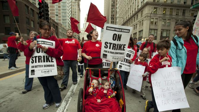 Two-year-old identical twins Colton and Lucas Jordan join thousands of public school teachers and their supporters as they march along Chicago's Michigan Avenue, protesting against Penny Pritzker, whom they accuse of benefiting from her position on the boards of both the Chicago Board of Education and Hyatt Hotels on Thursday, Sept. 13, 2012. (AP Photo/Sitthixay Ditthavong)