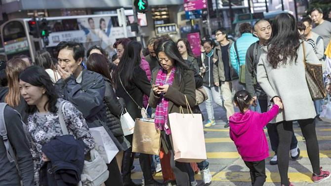 HKG. Hong Kong (China), 20/12/2014.- Shoppers carry bags as they cross an intersection on Nathan Road in Tsim Sha Tsui, one of the territory's main shopping districts, in Hong Kong, China, 20 December 2014. Locals and tourists alike are shopping during the last weekend before Christmas, a public holiday in Hong Kong. EFE/EPA/JEROME FAVRE