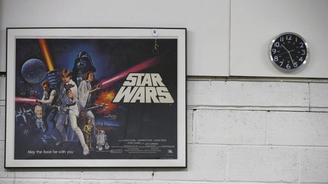 An original cinema poster from the first Star Wars film hangs on a wall ahead of an auction of Star Wars and film related toys at the Vectis auction house in Stockton-on-Tees