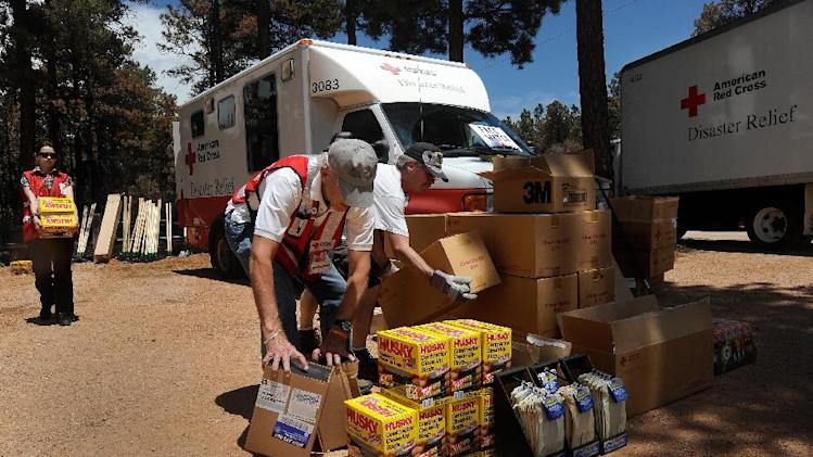 American Red Cross volunteers Dylan Scott, left, from Bowling Green, Ky., Peter Booth, of Colorado Springs, and Mike Cooper, of Fort Collins, stack supplies for returning residents at the re-entry station Tuesday, June 18, 2013, at the School in the Woods in Colorado Springs, Colo., as some residents were allowed to return to their homes Tuesday, June 18, 2013. The Black Forest fire has destroyed 502 homes and charred more than 22 square miles. It was 85 percent contained Tuesday. (AP Photo/The Colorado Springs Gazette, Christian Murdock) MAGS OUT