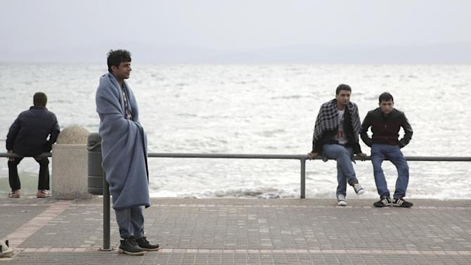 Baloch, from Pakistan, who arrived on the island of Kos, Greece, three days ago wears a blanket as he waits outside the police station, Wednesday, May 27, 2015. The European Union will seek to shift the migration burden away from Italy and Greece by relocating 40,000 asylum seekers to other EU countries, according to a draft document seen by The Associated Press Tuesday. (AP Photo/Petros Giannakouris)