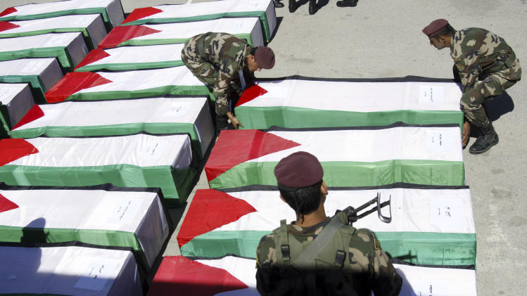 Members of the Palestinian security forces place a coffin on the ground containing the remains of one of 91 Palestinian militants transferred from Israel to the Palestinian Authority, in the West Bank city of Ramallah, Thursday, May 31, 2012. Israel transferred the bodies in an effort to induce Palestinian President Mehmoud Abbas to renew negotiations. Palestinian officials said all were killed either while carrying out suicide bombings or other attacks on Israeli targets. (AP Photo/Mohammed Ballas)