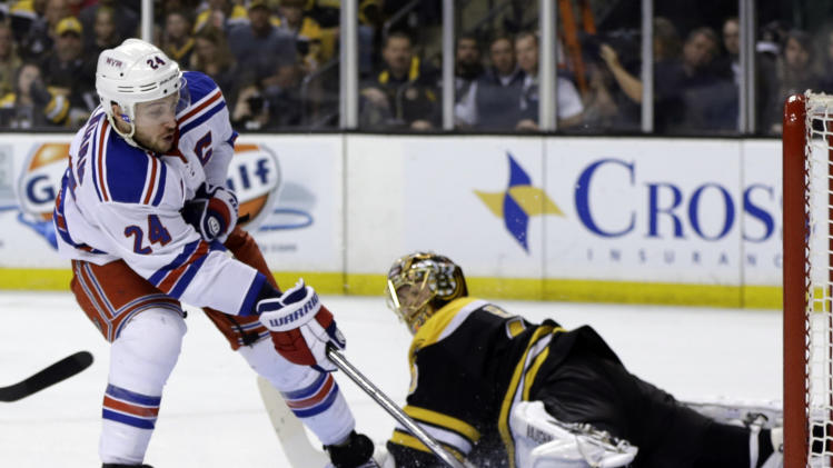 New York Rangers right wing Ryan Callahan, left, scores against Boston Bruins goalie Tuukka Rask, right, during the first period in Game 2 of the NHL Eastern Conference semifinal hockey playoff series in Boston, Sunday, May 19, 2013. (AP Photo/Elise Amendola)