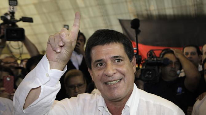 Paraguay's Colorado Party's Presidential candidate Horacio Cartes gestures before casts his vote during general elections in Asuncion, Paraguay, Sunday, April 21, 2013. The elections are an important milestone in Paraguay's attempt to regain the international acceptance it lost when neighboring nations objected to the fast-track removal of President Fernando Lugo. (AP Photo/Jorge Saenz)