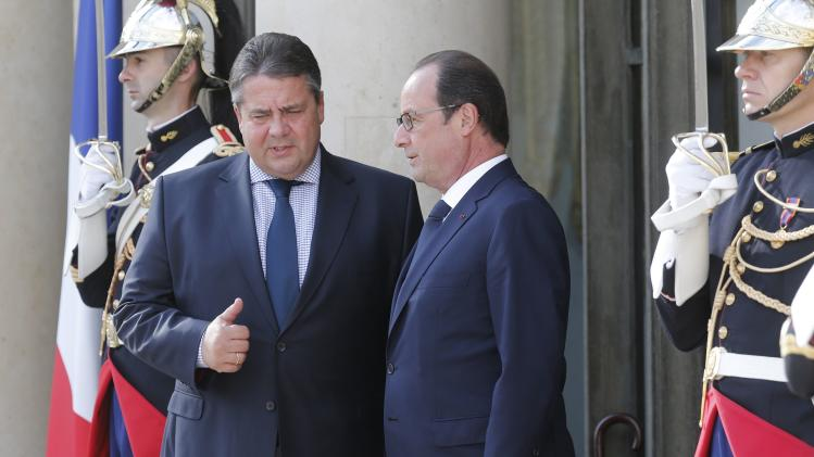 French President Hollande speaks with German SPD party head Gabriel before a meeting with European Socialist leaders at the Elysee Palace in Paris