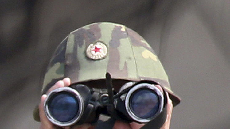 "A North Korean soldier uses a pair of binoculars to watch the South Korean side at the border village of Panmunjom in the demilitarized zone (DMZ) in South Korea Thursday, April 4, 2013. South Korea's defense minister said Thursday North Korea has moved a missile with ""considerable range"" to its east coast, but said it is not capable of hitting the United States. (AP Photo/Yonhap, Lee Jong-hoon)  KOREA OUT"