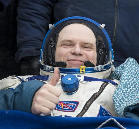 Former ISS commander Kotov of Russia sits in a chair outside the Soyuz TMA-10M capsule shortly after the landing in a remote area southeast of Zhezkazgan