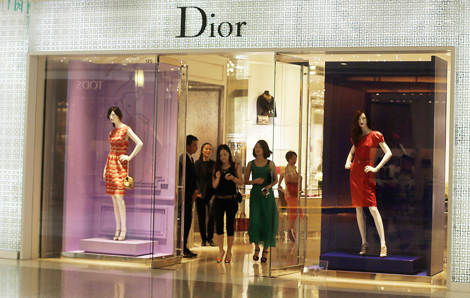 Shoppers exit a Dior shop Wednesday, June 13, 2012, in Shanghai, China. Chinese consumers can afford to splash out more on higher quality products, but also expect better value for money than in the past, according to a study by the American Chamber of Commerce. (AP Photo/Eugene Hoshiko)