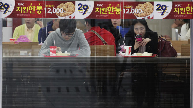 People eat at a fast food restrant in Seoul, South Korea, Friday, April 5, 2013. Outsiders might hear the opening notes of a war in the deluge of threats and provocations from North Korea, but to South Koreans it is a familiar song. Foreigners unused to North Korean rumblings have canceled trips to the Korean Peninsula. But to get South Koreans' attention, Pyongyang must compete with the economy, celebrity scandals, baseball games and cherry blossoms. (AP Photo/Ahn Young-joon)