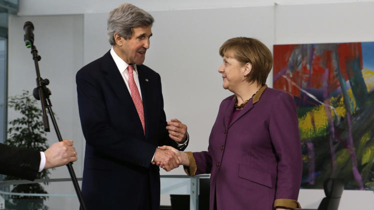 A microphone is taken away at the end of a news conference as U.S. Secretary of State John Kerry and German Chancellor Angela Merkel shake hands at the Chancellery in Berlin on Tuesday, Feb. 26, 2013. Berlin is the second stop in Kerry's first trip overseas as secretary. (AP Photo/Jacquelyn Martin, Pool)
