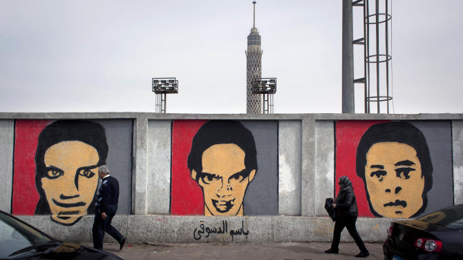 "Two Egyptian pedestrians pass by murals with pictures depicting some of the slain Ultras members supporting the Cairo-based Al-Ahly club, who were killed in a soccer riots last year, that covers the sidewall of their soccer club facility in Cairo, Egypt, Thursday, Feb. 14, 2013. Arabic at the mural reads the name of the slain soccer fan ""Basim al-Desouky."" (AP Photo/Nasser Nasser)"