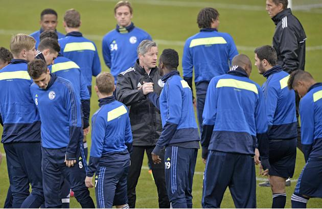 Schalke head coach Jens Keller shakes hands with his players during a training session one day ahead  the Champions League Group E soccer match between FC Schalke 04 and FC Basel in Gelsenkirchen, Ger