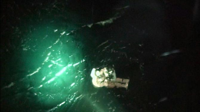 In this photo released by Yeosu Martime Poilice via Yonhap, a maritime policeman, wearing black helmet at top, rescues a North Korean crew member of a sunken cargo ship in the sea, off Yeosu, South Korea, Friday, April 4, 2014. The Mongolian-flagged cargo ship, which was carrying 16 North Korean crew members, remains missing after it sent a distress signal early Friday in waters about 130 kilometers (80 miles) south of the southern port city of Yeosu, the coast guard said in a statement. Three people were rescued and identified themselves as part of a 16-member North Korean crew on the ship, the statement said. (AP Photo/ Yeosu Maritime Police via Yonhap) KOREA OUT