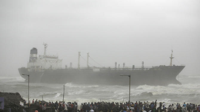 People look at Indian ship Pratibha Cauvery that ran aground with people on board, reportedly due to strong winds on the Bay of Bengal coast in Chennai, India, Wednesday, Oct. 31, 2012. More than 100,000 people were evacuated from their homes Wednesday as a tropical storm hit southern India from the Bay of Bengal, officials said.Rain lashed the region and strong winds uprooted trees in some places. Weather officials said the storm packed winds of up to 100 kilometers (60 miles) per hour as it made landfall near Chennai, the capital of Tamil Nadu state. (AP Photo/Arun Sankar K)