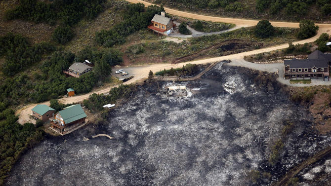 Untouched homes stand next to the ashes of a home destroyed by a wildfire that swept through a development near Rockport, Utah, Wednesday, Aug. 14, 2013. The wildfire, which appears to have been started by lightning, destroyed a dozen homes on Tuesday, plus another home overnight. (AP Photo/Deseret News, Ravell Call) SALT LAKE TRIBUNE OUT; MAGS OUT