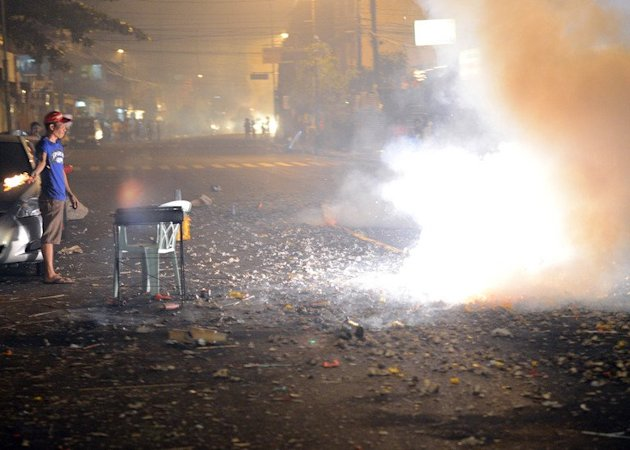Revellers set off firecrackers to usher in New Year's Day in Manila, early on January 1, 2013. Celebratory gunfire killed a four-year-old boy and more than 200 others were injured by powerful firecrackers in typically rowdy New Year celebrations in the Philippine capital