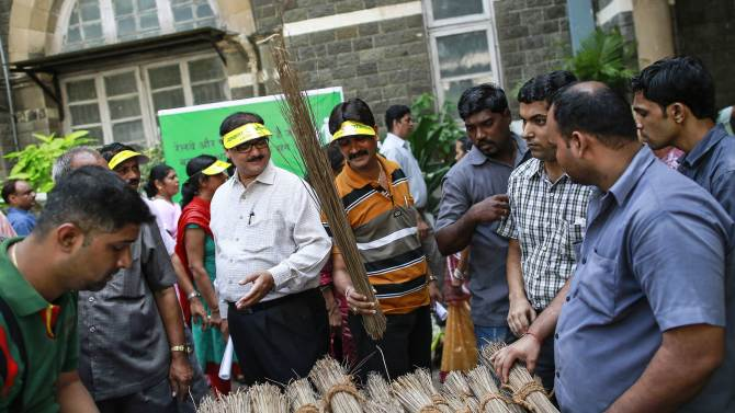 Employees from various departments collect brooms before a cleanliness drive at an Indian Railways office in Mumbai